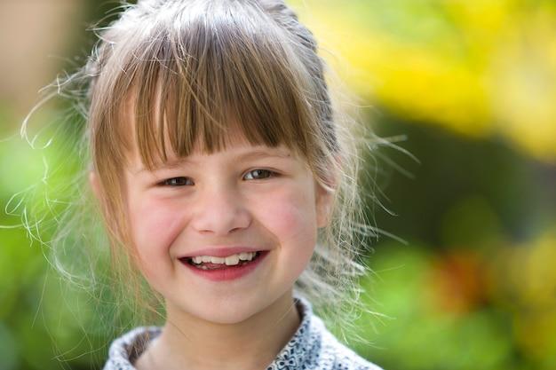 Dziecko dziewczynka z szarymi oczami, uśmiechając się do kamery na zewnątrz