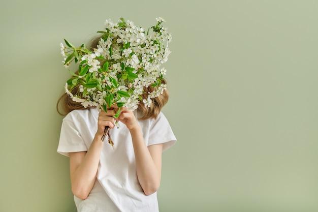 Dziecko dziewczynka z wiosennych białych kwiatów kwitnących gałęzi wiśni