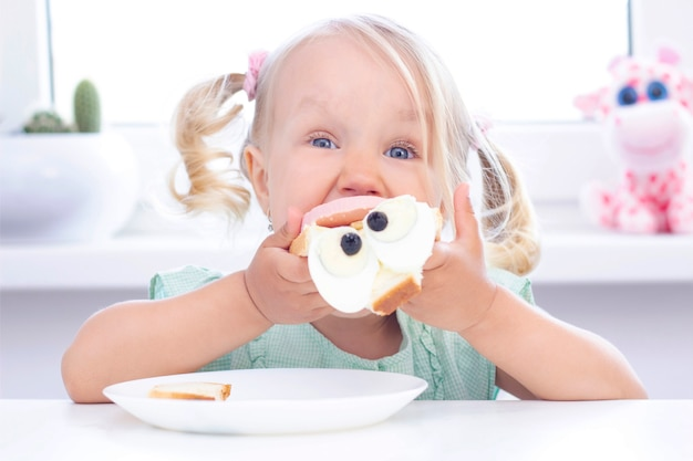 Dziecko dziewczyny blondynka je kanapkę przy stołem na świetle