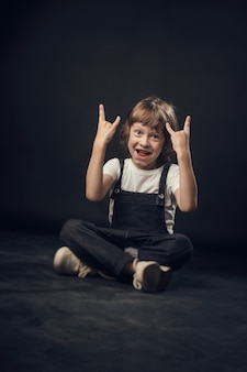 Dziecko emocjonalnie pozuje do kamery w studio na białym tle