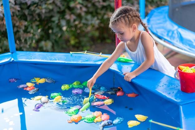 Dziecko fisher łapanie plastikowej zabawki ryby na basenie park rozrywki letni dzień mała dziewczynka baw się dobrze na wędkowaniu karnawał festiwal rozrywka dla dzieci