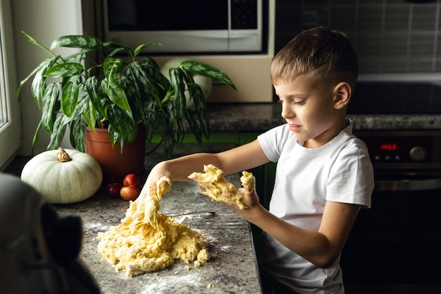 Dziecko gotuje w kuchni. chłopiec pomaga zrobić ciasto na ciasteczka. niegrzeczny facet. aktywność wewnętrzna.