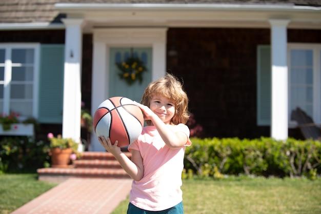 Dziecko gra w koszykówkę. dziecko pozuje z koszem na zewnątrz.