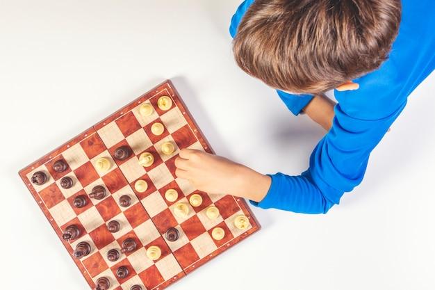 Dziecko gra w szachy na szachownicy