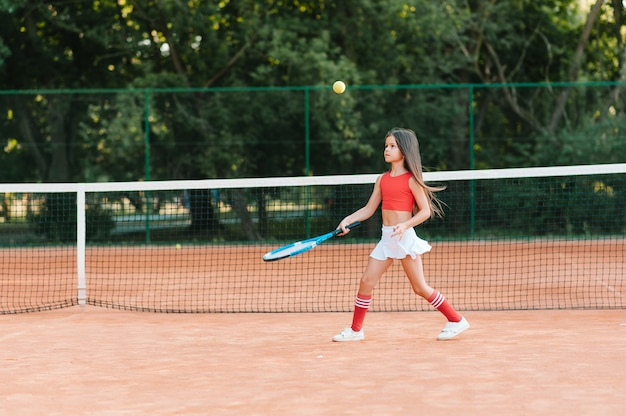 Dziecko grające w tenisa na korcie zewnętrznym. mała dziewczynka z rakietą tenisową i piłką w klubie sportowym. aktywne ćwiczenia dla dzieci