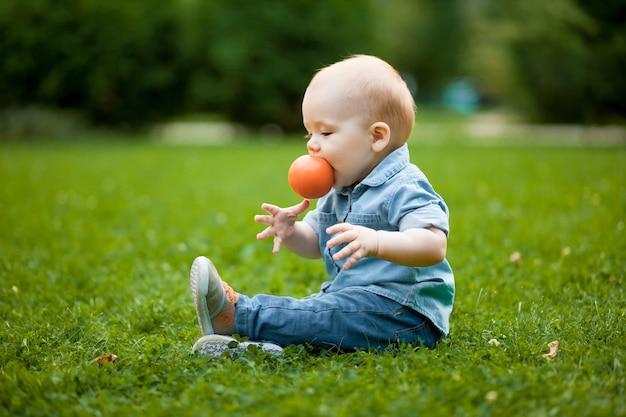 Dziecko gryzie piłkę na trawniku w parku