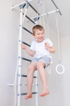 Dziecko huśta się na huśtawce na szwedzkiej ścianie i uprawia sport w domu, pojęcie sportu i zdrowia