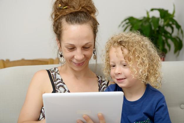 Dziecko i jej mama korzystają z tabletu