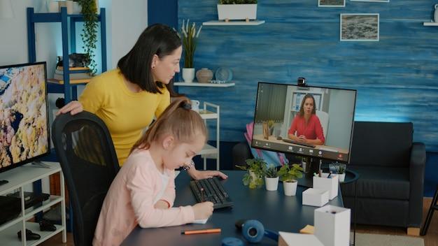 Dziecko i matka korzystające z połączenia wideo z nauczycielem podczas lekcji online