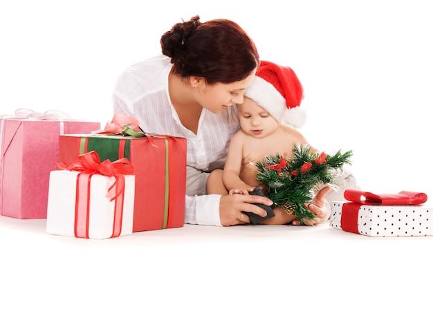 Dziecko i matka z prezentami świątecznymi na białej ścianie