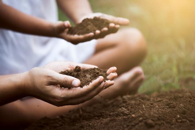 Dziecko i rodzic trzymają ziemię i przygotowują ziemię do posadzenia drzewa razem