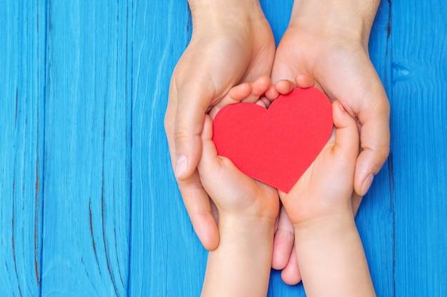 Dziecko i tata ręce, trzymając czerwone serce