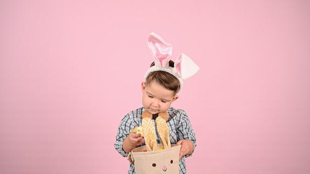 Dziecko i wielkanoc, na różowym tle. wysokiej jakości zdjęcie