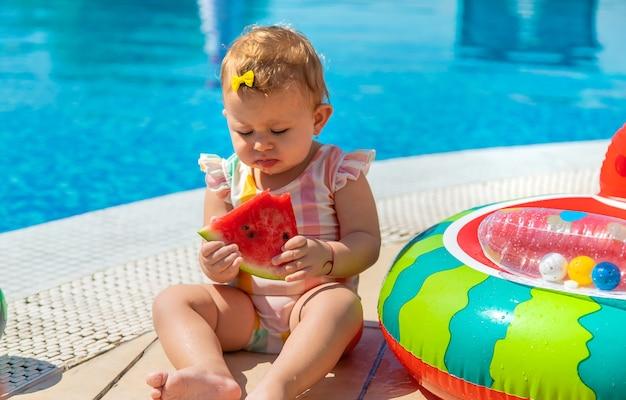 Dziecko je arbuza przy basenie. selektywne skupienie. dzieci.