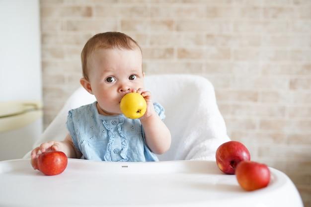 Dziecko je owoc. mała dziewczynka gryzienie żółte jabłko siedzi w białym wysokim krześle w słonecznej kuchni