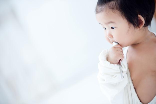 Dziecko je swoje jedzenie dla niemowląt na białym stole.