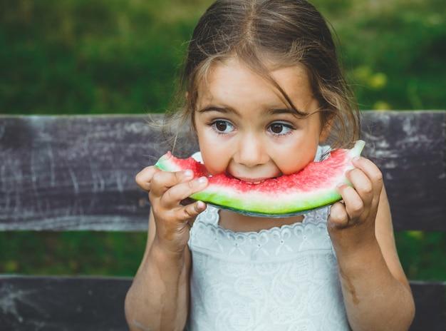 Dziecko jedzenie arbuza w ogrodzie. dzieci jedzą owoce na świeżym powietrzu. zdrowa przekąska dla dzieci. dziewczynka bawi się w ogrodzie gryzie kawałek arbuza.