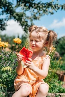 Dziecko jedzenie arbuza w ogrodzie. dzieci jedzą owoce na świeżym powietrzu. zdrowa przekąska