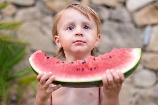 Dziecko jedzenie arbuza w ogrodzie podczas letnich wakacji. dzieci jedzą owoce na świeżym powietrzu. zdrowa przekąska dla dzieci. mały chłopiec degustuje kawałek arbuza.
