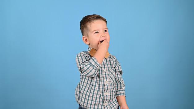 Dziecko jedzenie cukierków na niebieskim tle. wysokiej jakości zdjęcie