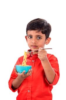 Dziecko jedzenie makaronu, indian kid jedzenie makaronu z widelcem na białej ścianie