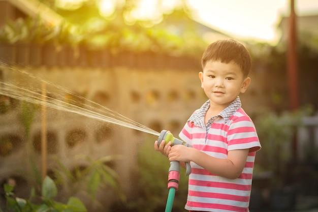Dziecko jest podlewanie do roślin w doniczce w domu.