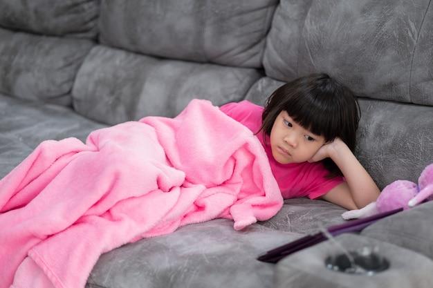 Dziecko jest uzależnione od tabletu, mała dziewczynka gra na smartfonie, dziecko korzysta z telefonu, ogląda kreskówkę