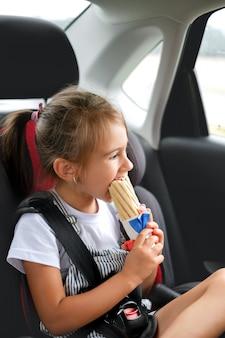Dziecko jest zapinane pasem bezpieczeństwa w foteliku samochodowym i zjada francuską bułkę