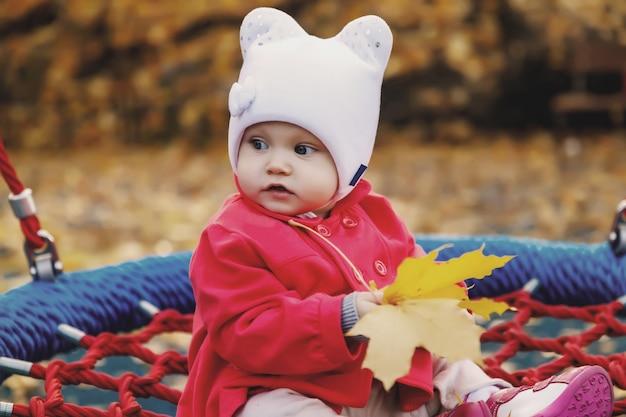 Dziecko jeździ na huśtawce z żółtymi jesiennymi liśćmi
