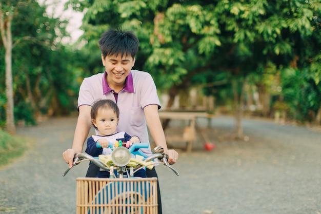 Dziecko jeździć na rowerze z ojcem.