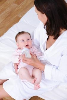 Dziecko karmi się butelką przez matkę