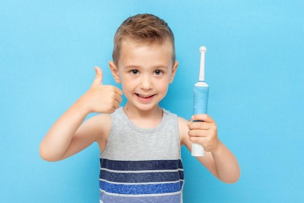 Dziecko kciuk z elektryczną szczoteczką do zębów na niebiesko