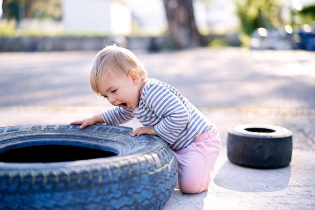 Dziecko klęczy i opiera się o oponę samochodu na parkingu