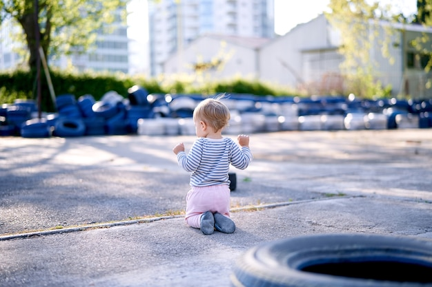 Dziecko klęczy na tle opon samochodowych na parkingu widok z tyłu