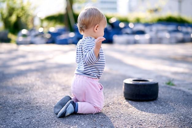 Dziecko klęczy przy obręczy samochodu na parkingu