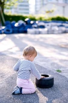 Dziecko klęka i dotyka obręczy auta na parkingu