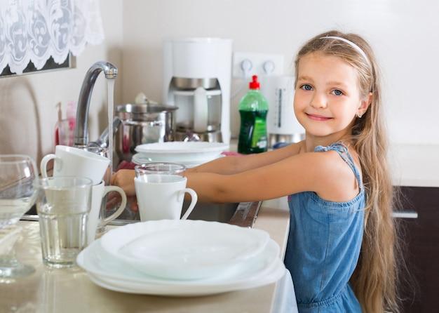 Dziecko kobiece czyszczenie naczyń w domu