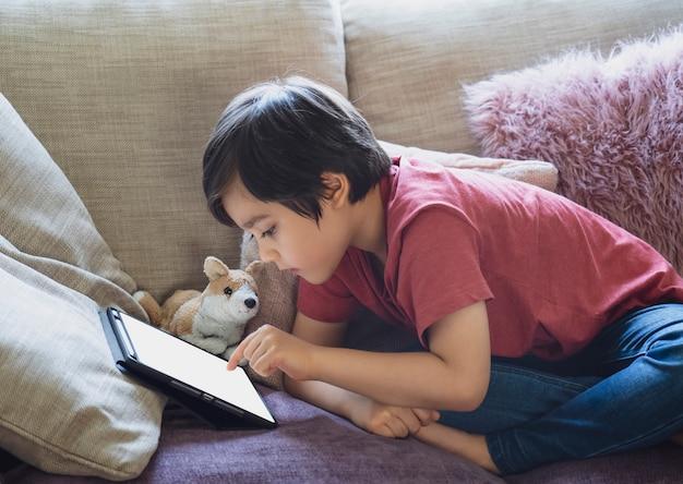 Dziecko korzystające z tabletu do odrabiania lekcji, dziecko leżące na kanapie, relaksujące się w domu, oglądające bajki lub grające w gry na cyfrowym tablecie, szkolnictwo domowe, dystans społecznościowy, e-learningowa edukacja online