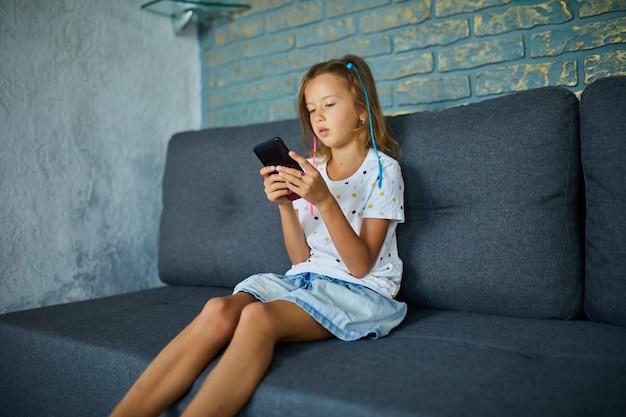 Dziecko korzystające z telefonu komórkowego na kanapie w nowoczesnym i jasnym mieszkaniu, młoda dziewczyna gra na smartfonie w domu, problem uzależnienia od gadżetów