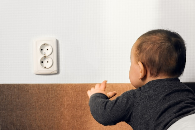 Dziecko kraul stawia palce elektrycznego gniazdkowego ściennego ujścia zagrożenia niebezpieczeństwa bezpieczeństwa domu pojęcie