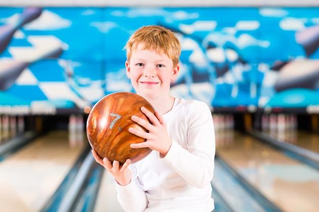 Dziecko kręgle z piłką w alei