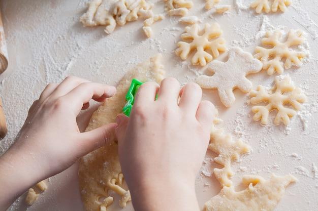 Dziecko kroi ciasteczka w kształcie płatków śniegu. świąteczne pieczenie koncepcji