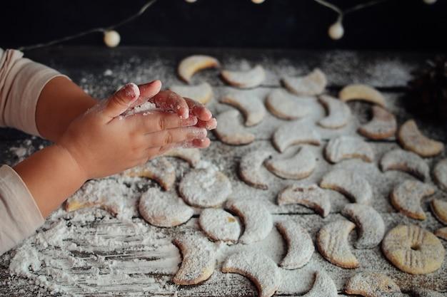 Dziecko kropi sproszkowane cukrowe ciasteczka. ręce i mąka dla dzieci. dziecko przygotowuje świąteczne ciasteczka. słodkie dłonie dziecka. dziecko i ciasteczka.