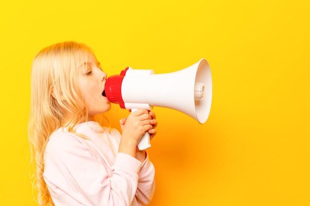 Dziecko krzyczy przez megafon vintage. koncepcja komunikacji. tło błękitnego nieba jako kopia o wpisanie tekstu.