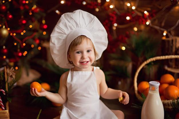 Dziecko kucharz przygotowuje pierniki. wesołych świąt, mandarynek, choinki