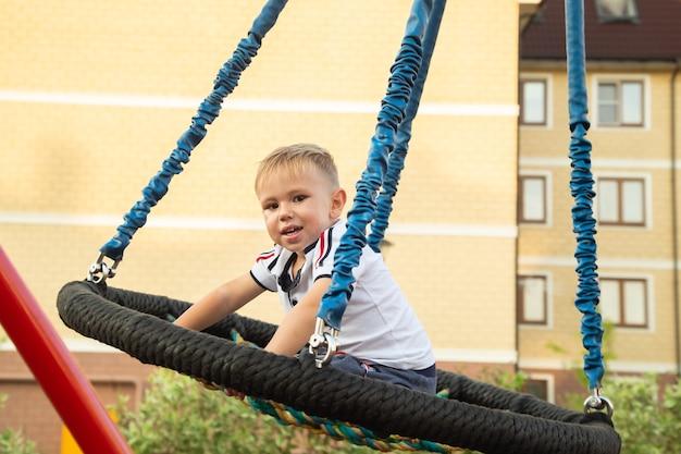 Dziecko ładny chłopiec kaukaski jazda huśtawka na placu zabaw w pobliżu miasta