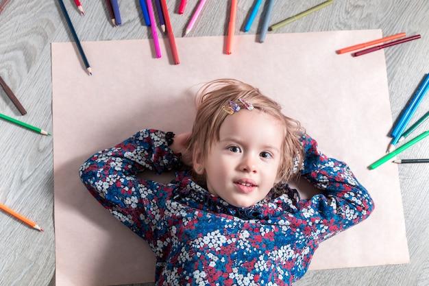 Dziecko leżące na podłodze na papierze w pobliżu kredek malowanie dziewczynki, rysowanie koncepcja kreatywności