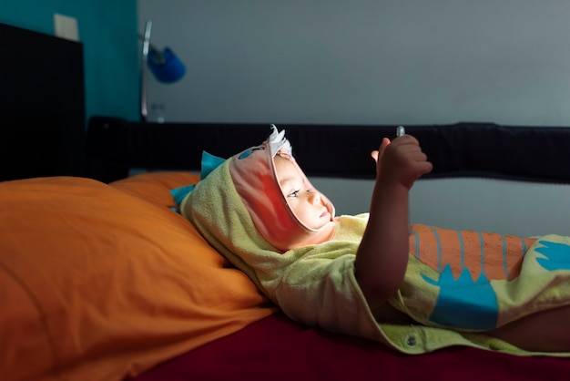 Dziecko leżące w łóżku w szlafroku oglądając filmy na tablecie