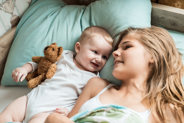 Dziecko leżące w łóżku ze swoją siostrą