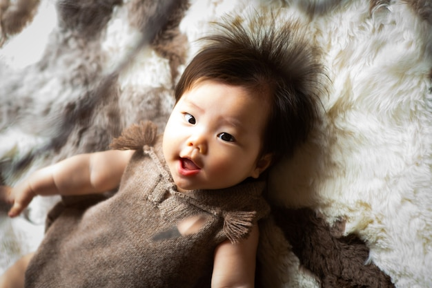 Dziecko leży na dywanie uśmiechnięte i patrzy w górę